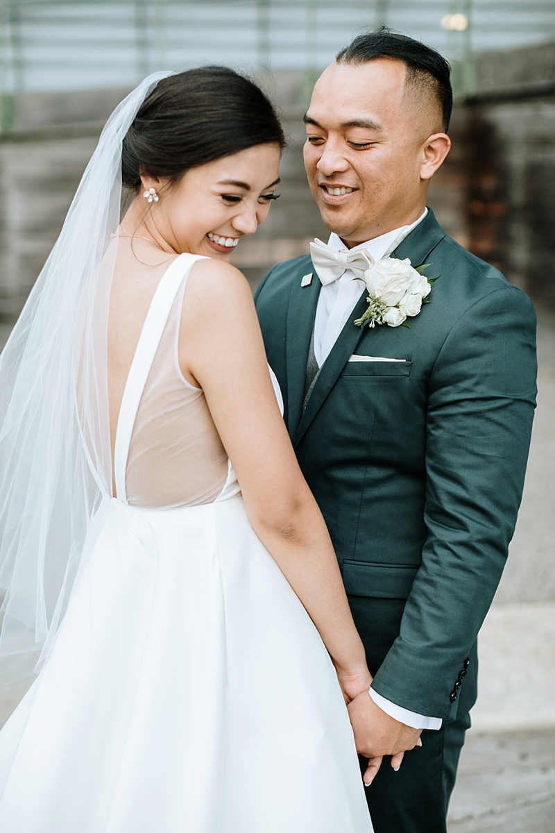 Adorable moment between bride wearing BHLDN dress and groom on their wedding day at Decker Half Moone Center in Norfolk Virginia