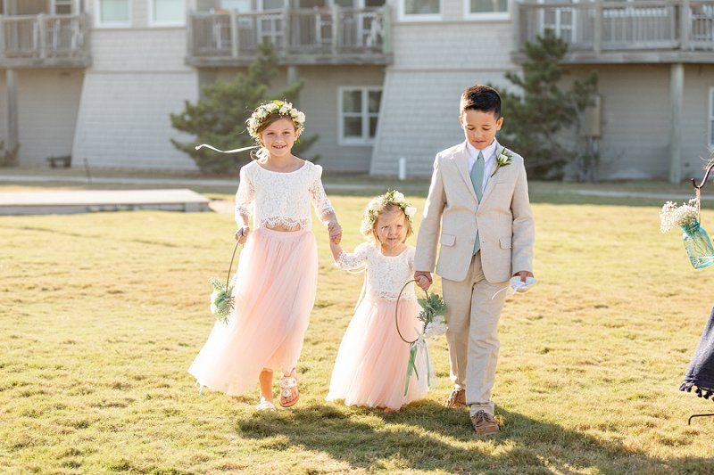 Adorable flower girls in lace tops and pink tulle skirts holding a ring shaped beach flower bouquet at Sanderling Resort in Outer Banks