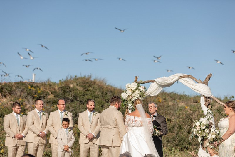 Romantic beachside wedding ceremony at Sanderling Resort in Outer Banks with driftwood ceremony arch and white drapery