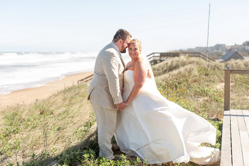 Beautiful plus size bride wearing strapless wedding dress with sweetheart neckline and full satin skirt for beachside wedding