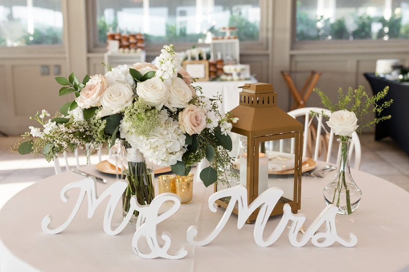 Elegant and timeless fall beach wedding reception for bride and groom table with gold lantern and bridal bouquet