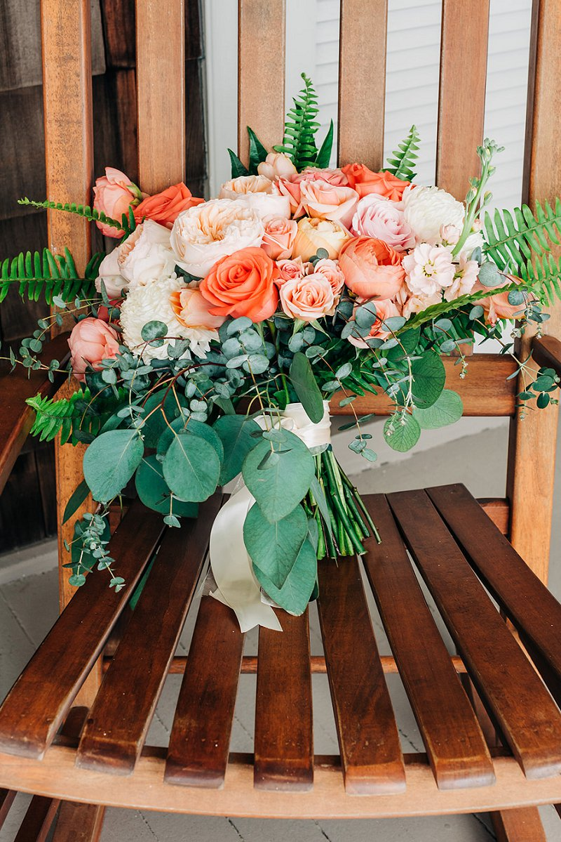 Gorgeous orange and coral peach bridal bouquet with fern and eucalyptus for destination beach wedding