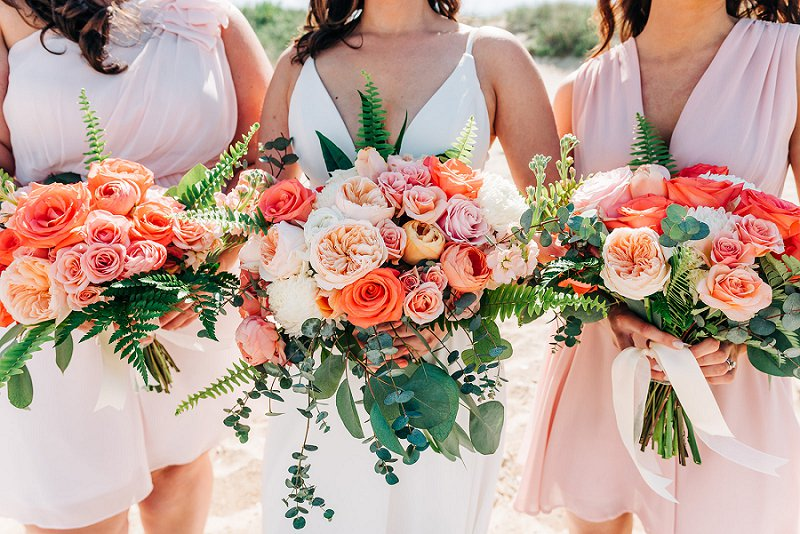 Gorgeous orange and coral bouquets with fern and eucalyptus for destination beach wedding