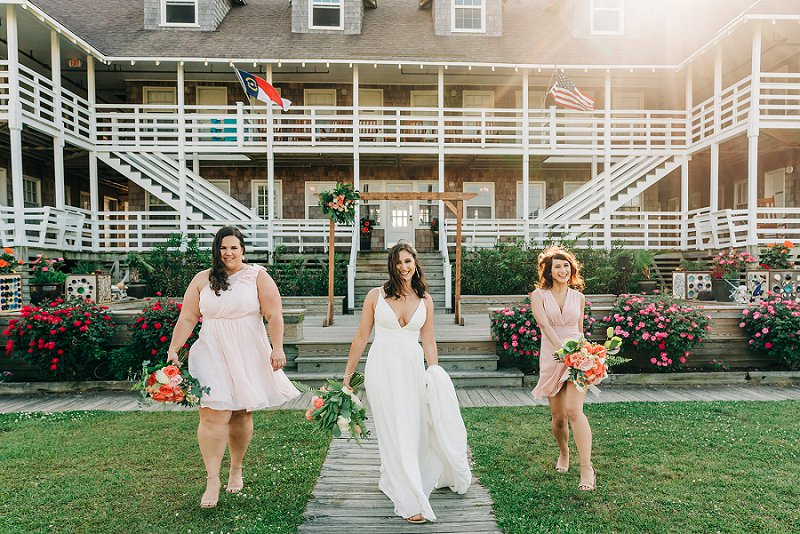 Beautiful and cheerful wedding party with bridesmaids in peach dresses at First Colony Inn in Outer Banks
