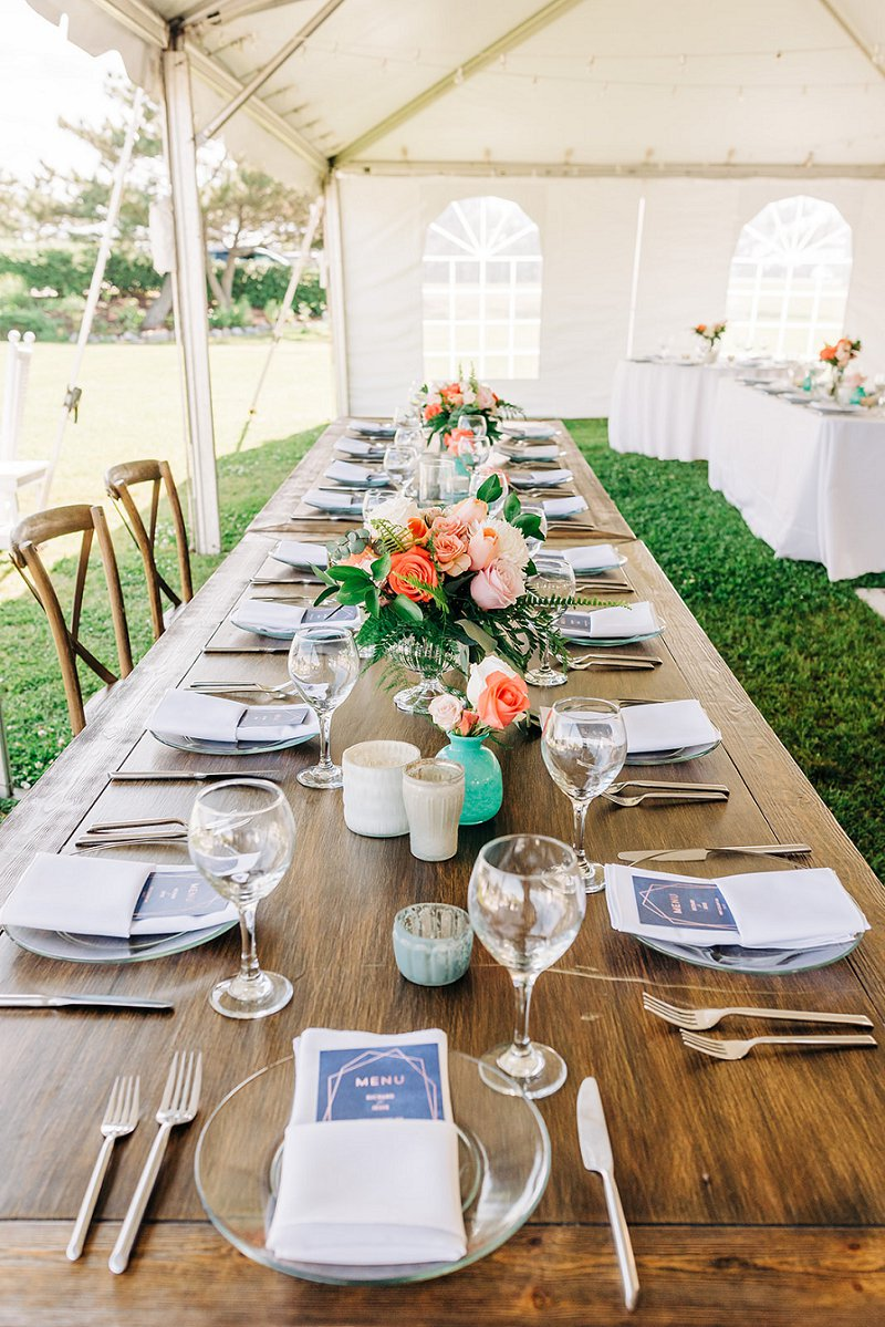 Orange peach and coral flower centerpieces for long wedding reception farm tables on the beach