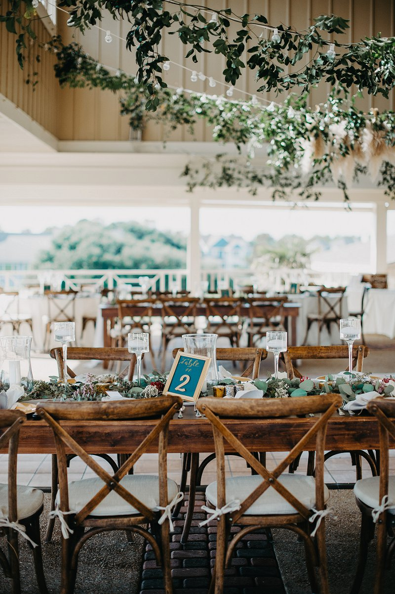 Lovely open air wedding reception with wooden farm tables and x back chairs