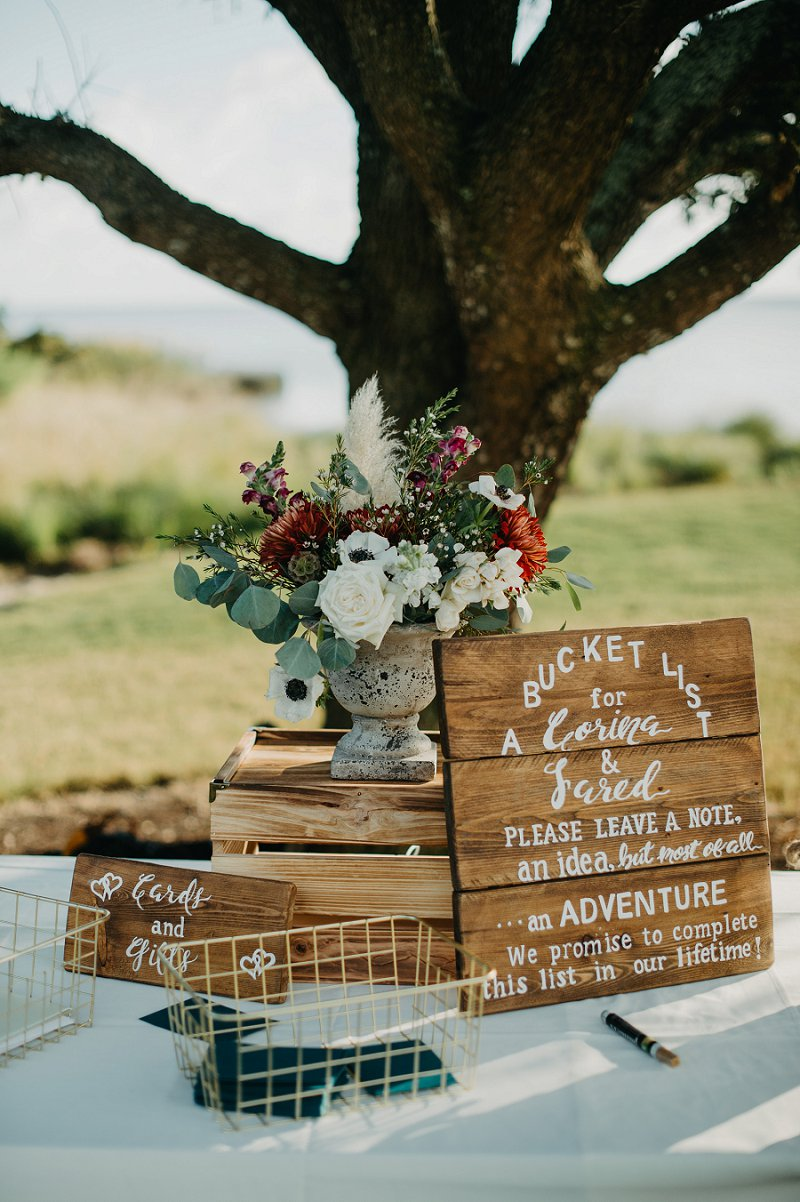 Unique Bucket List wedding guestbook idea with boho wedding flowers and wooden signs