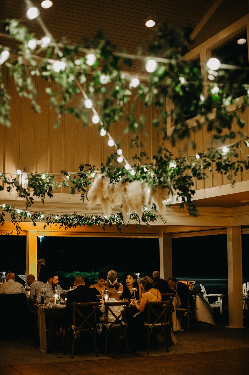 Outdoor pagoda wedding reception with bistro lights and hanging pampas grass in the Outer Banks