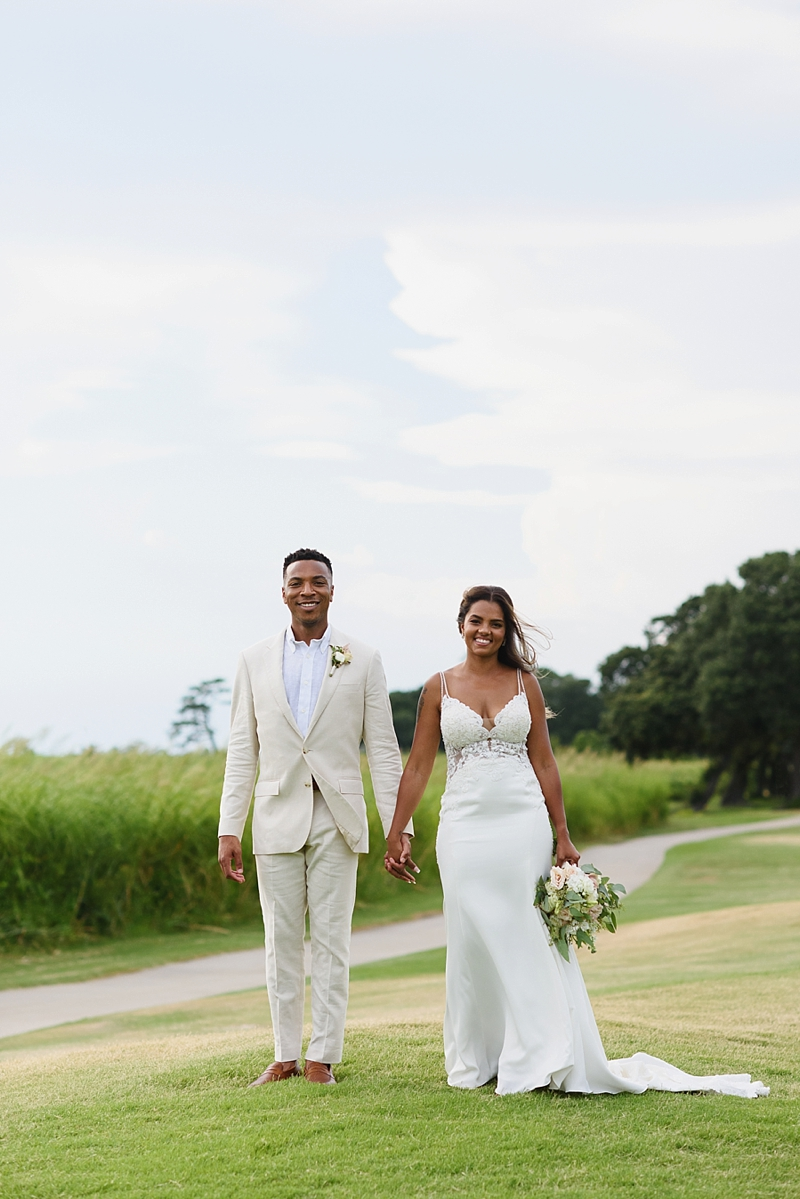 Bride wearing fitted Essence of Australia wedding dress with spaghetti straps and semi transparent bodice for elegant beach house wedding