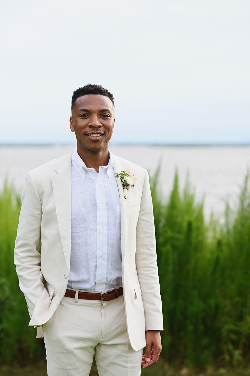 Handsome black groom wearing a tan linen suit and no necktie for an Outer Banks beach house wedding