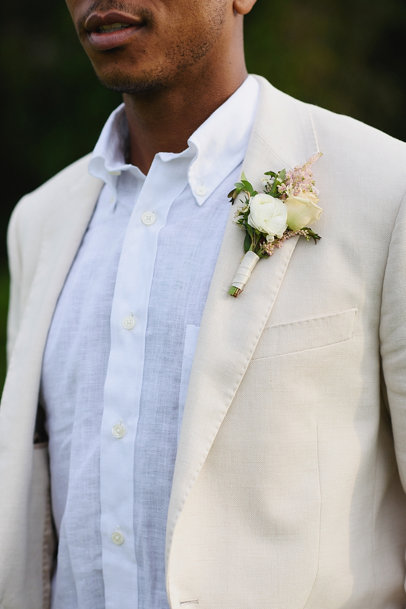 White and pink boutonniere on beige linen suit for beach groom