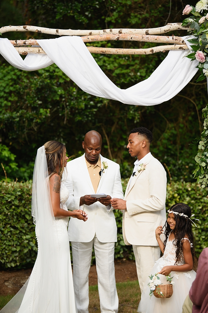 Outdoor beach house wedding ceremony with birch arch and drapery in the Outer Banks