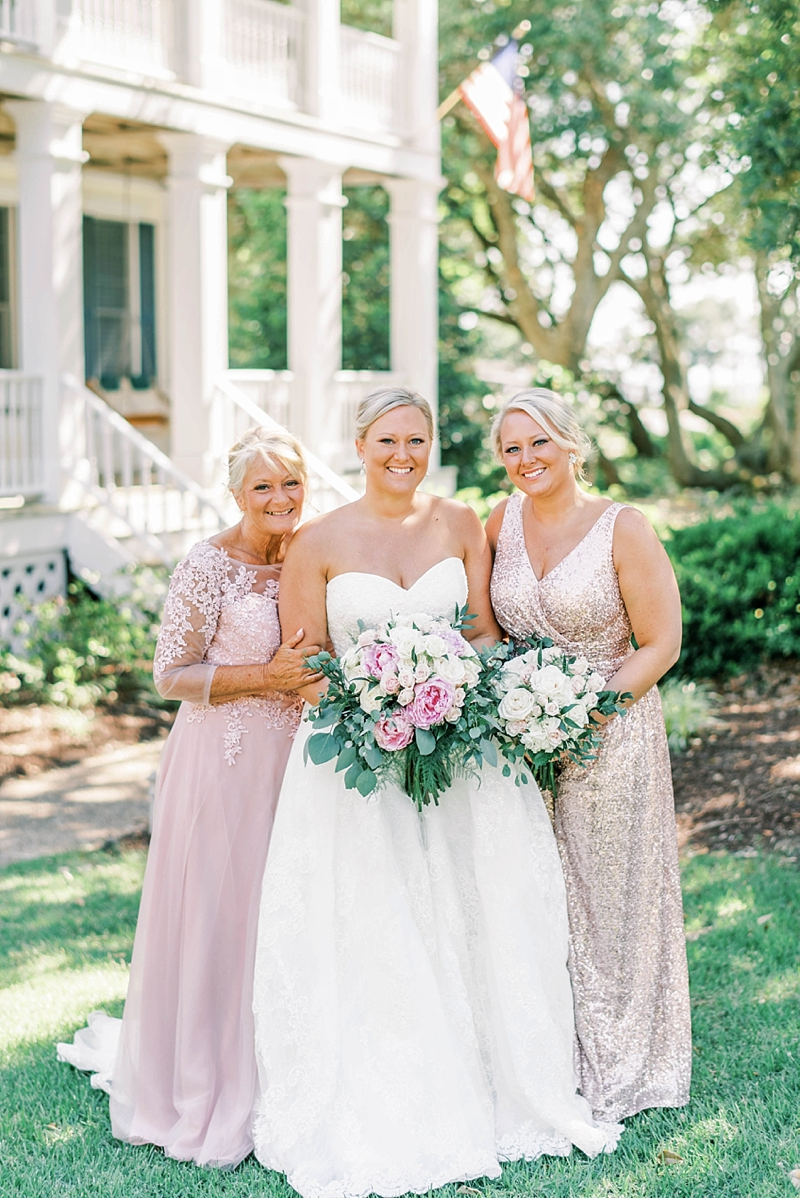 Beautiful photo moment between bride and her mom and sister during her COVID affected wedding in the Outer Banks