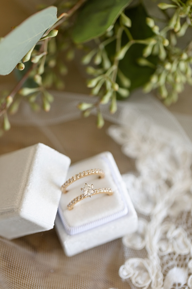 Matching diamond embedded gold wedding rings with a solitaire diamond engagement ring in a white velvet ring box