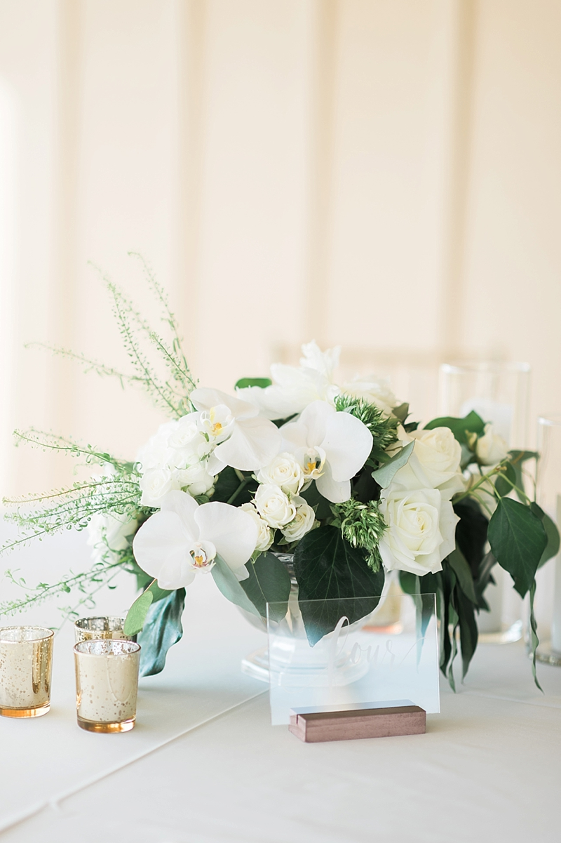 Small low wedding flower centerpiece with orchids and roses surrounded by clear acrylic table number and metallic gold candle votives