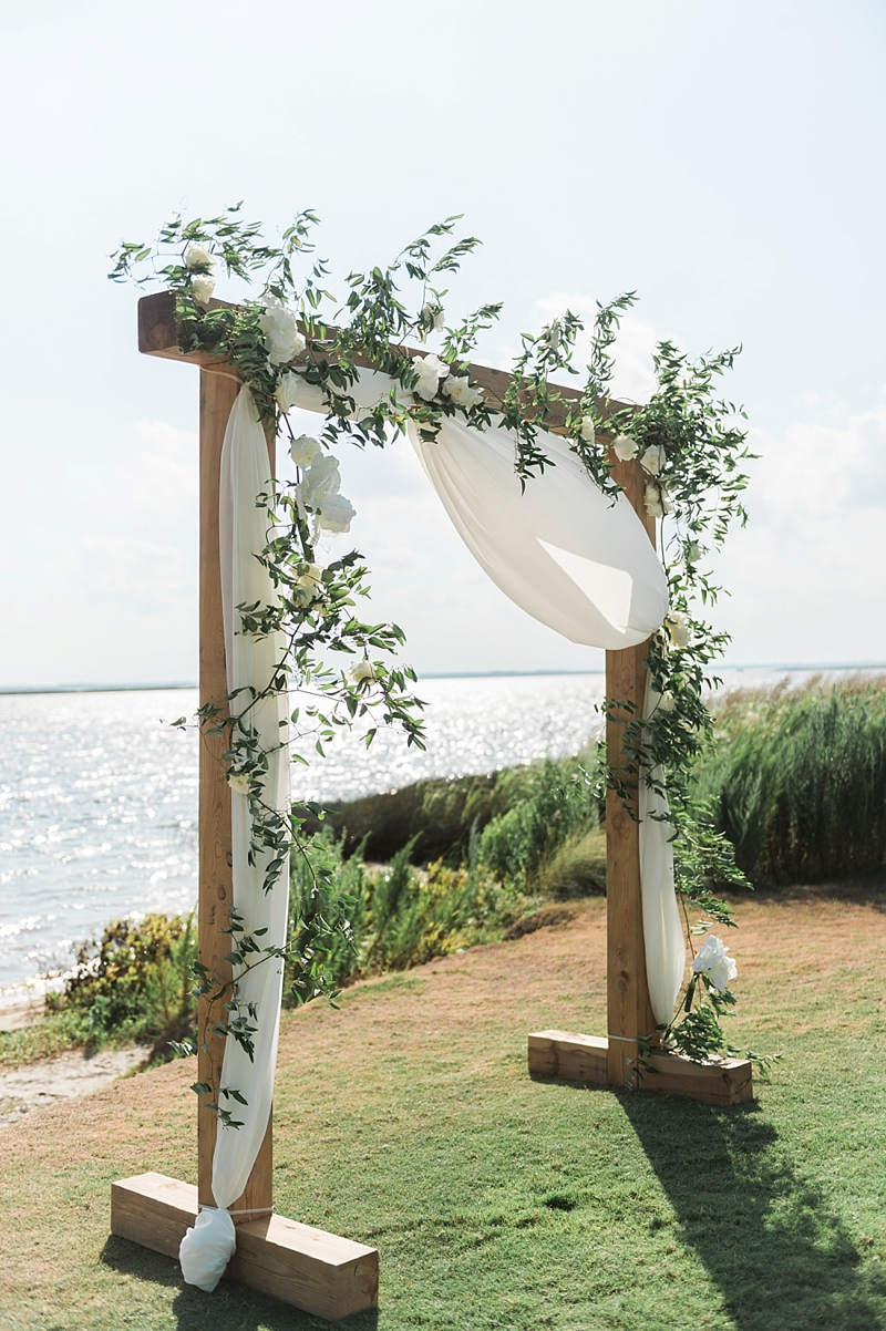 Simple and lovely wedding ceremony arch with greenery and draping for elegant COVID wedding in Outer Banks