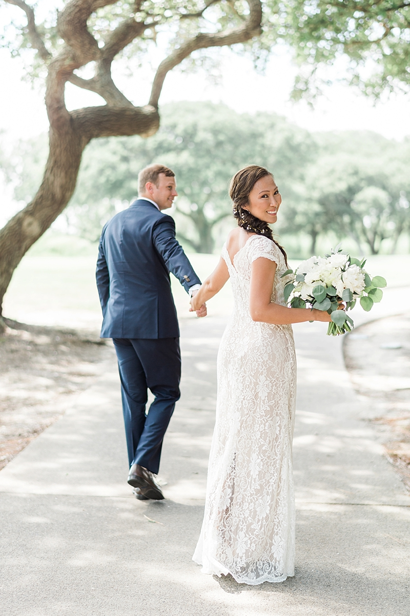 Bride wearing a long braided ponytail with flowers in it and a long lace fitted dress with short sleeves for COVID wedding day