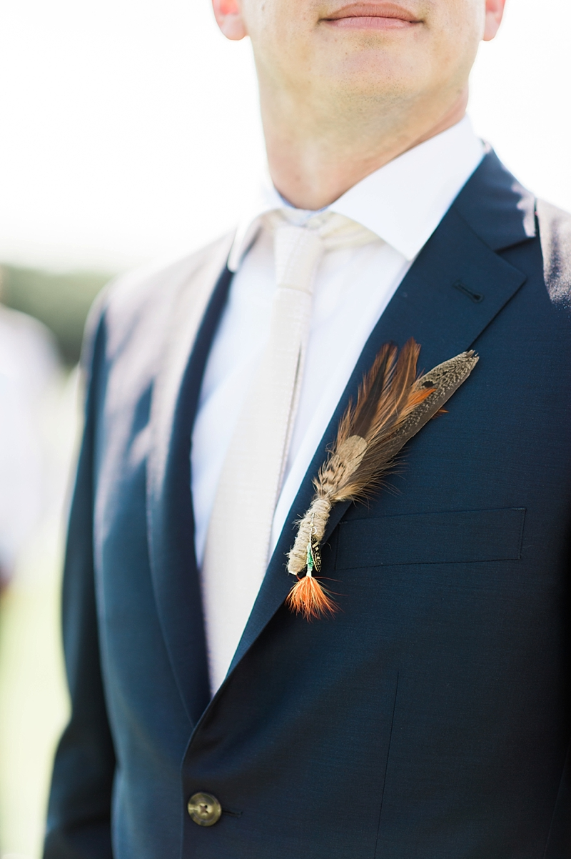 Unique fishing inspired alternative groom boutonniere with feather and a fishing lure