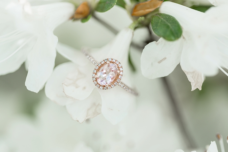 Round oval halo engagement ring with rose gold band embedded with small diamonds