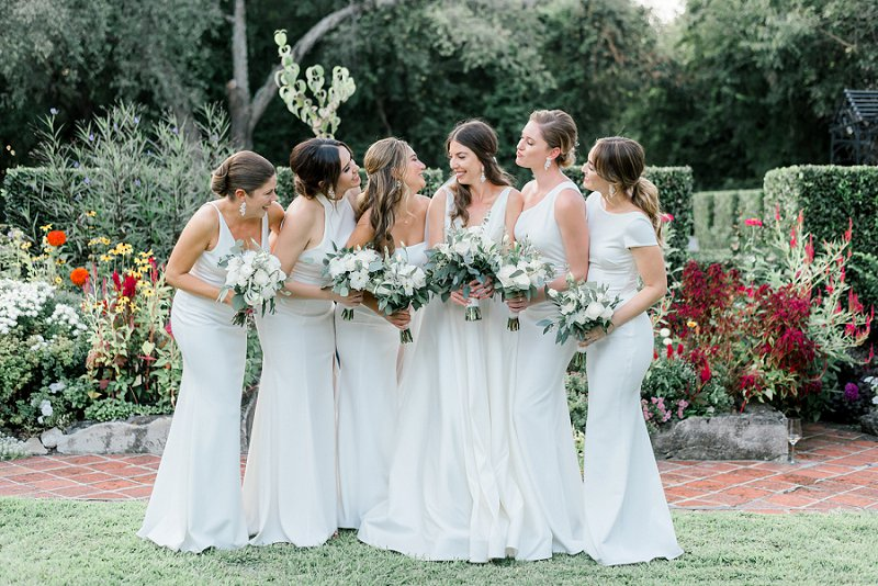 Bridesmaids in all white dresses from BHLDN  holding white bouquets for timeless classic wedding in Virginia