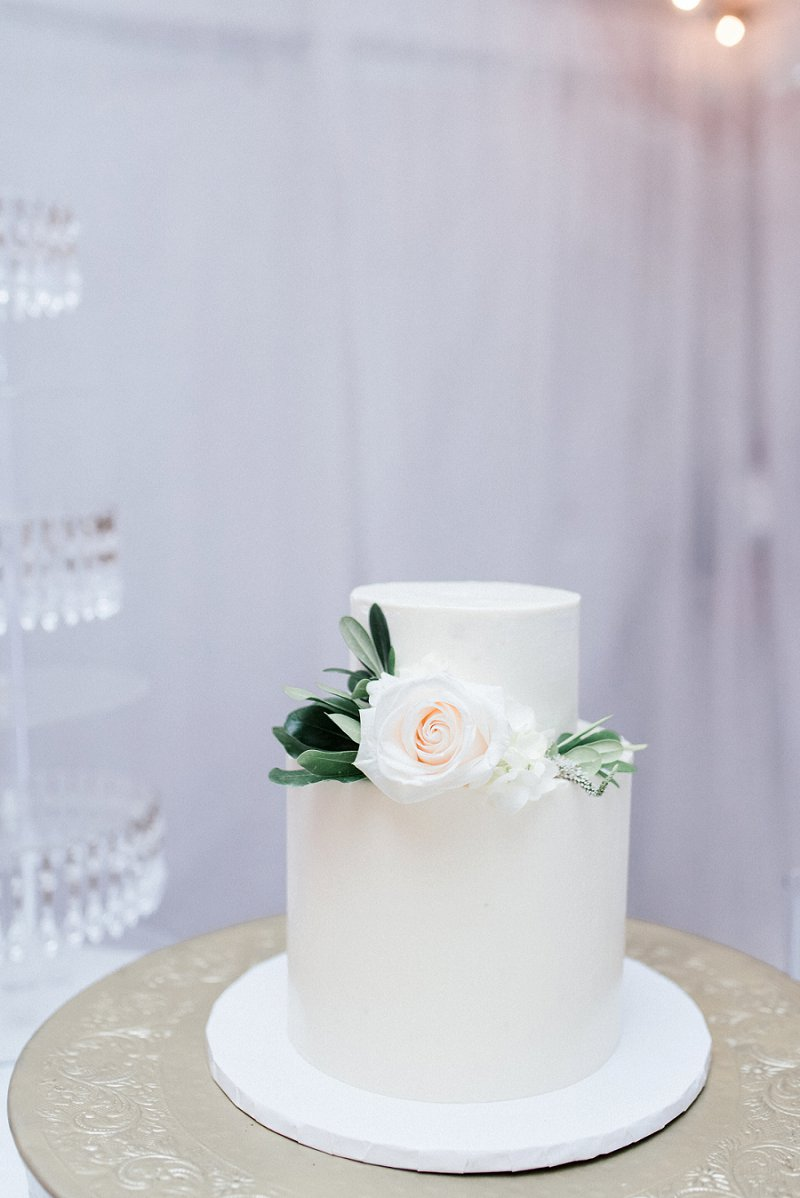 Simple two tiered white wedding cake with small floral decor for classic wedding