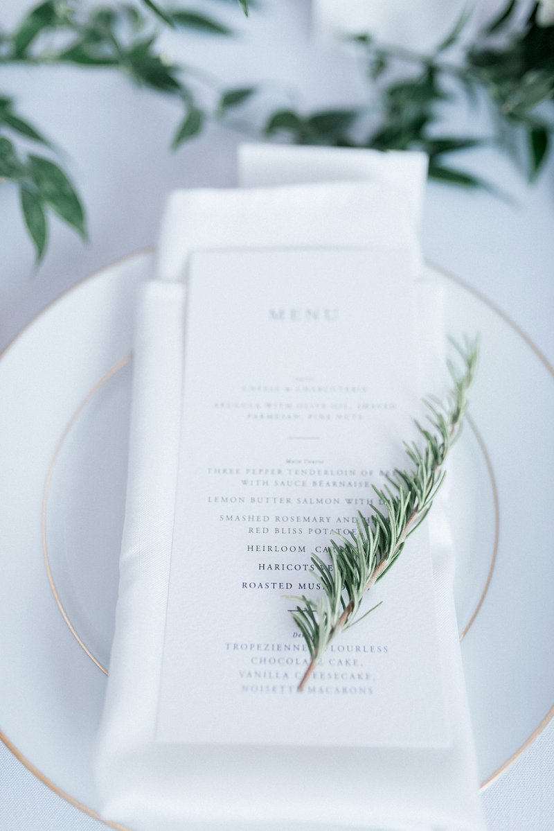 Classic black and white wedding menu card with rosemary sprig  and white napkin for timeless monochromatic wedding