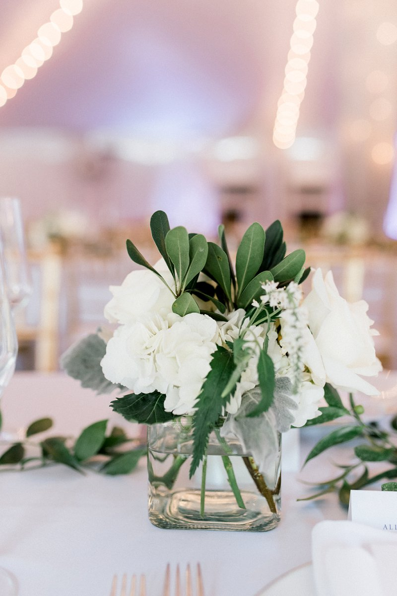 Simple small wedding reception floral centerpiece in glass vase with white flowers