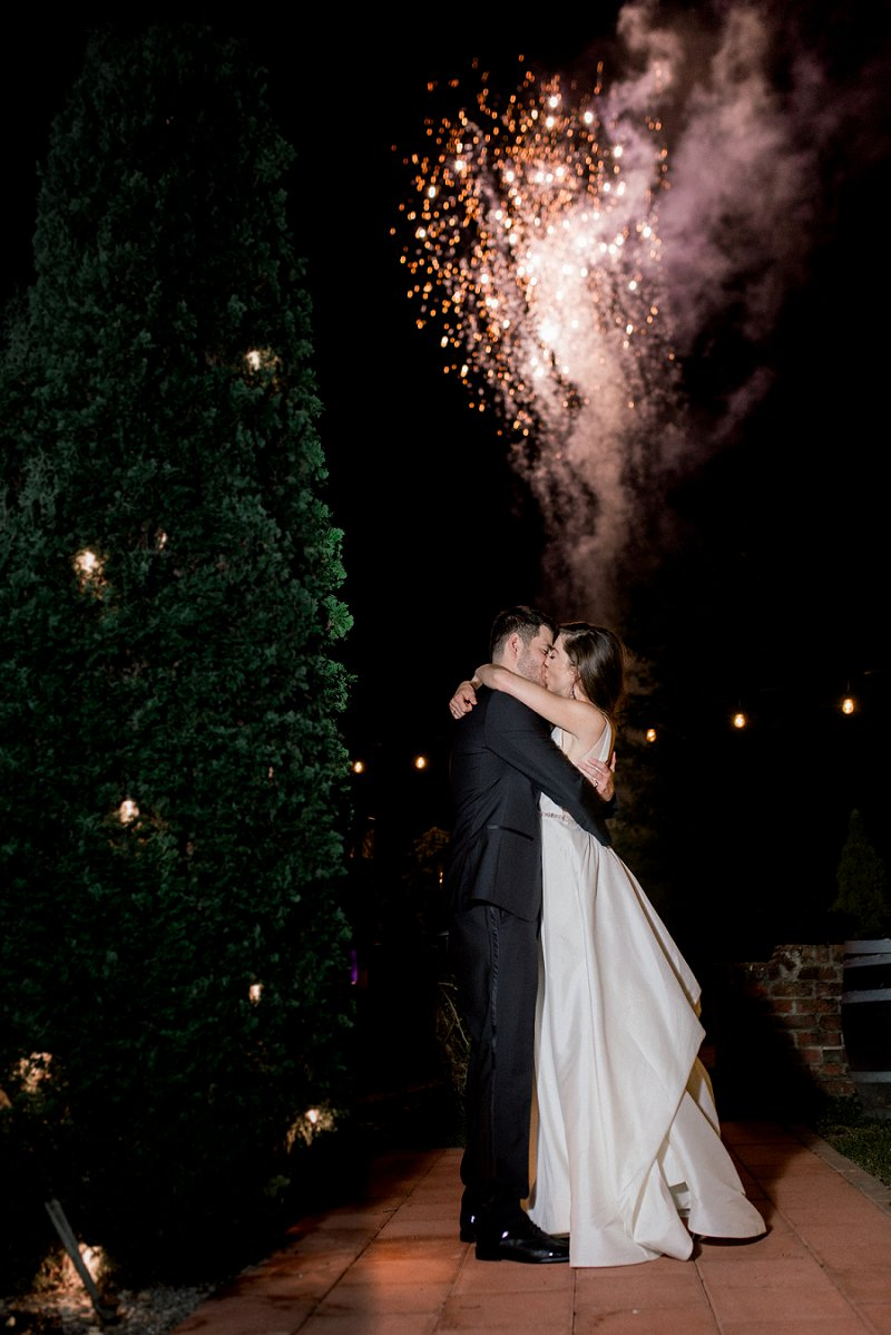 Epic wedding photo moment of bride and groom kissing in front of fireworks in Virginia wedding