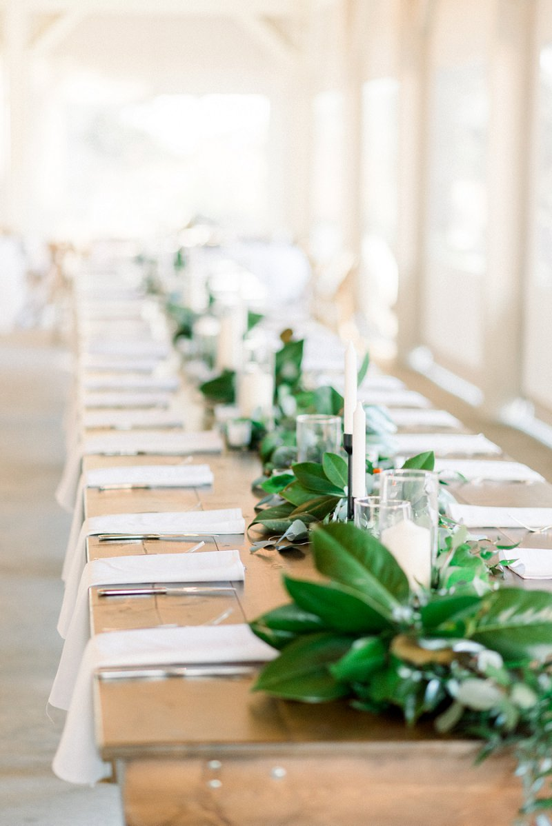 Modern rustic wedding reception farm table with magnolia leaves and candles
