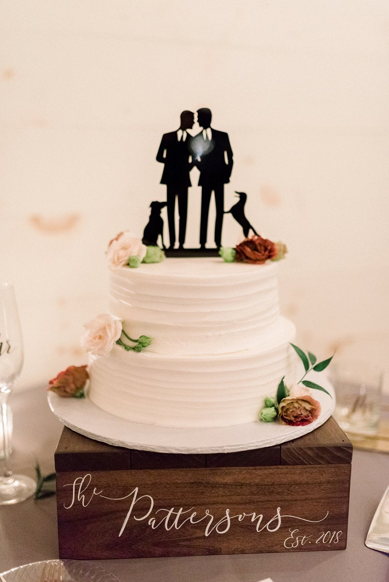 Simply textured two tiered white wedding cake with gay wedding cake topper of two grooms and their two dogs sitting on a wooden cake box stand