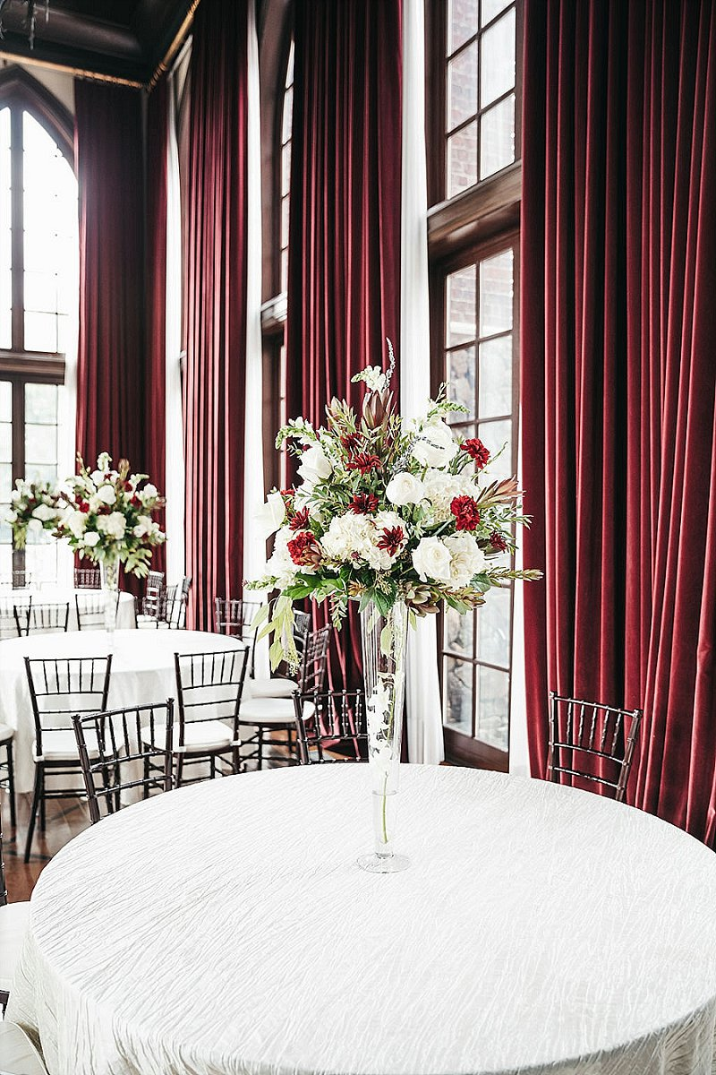 Tall wedding floral centerpieces with red and white flowers for a classic ballroom