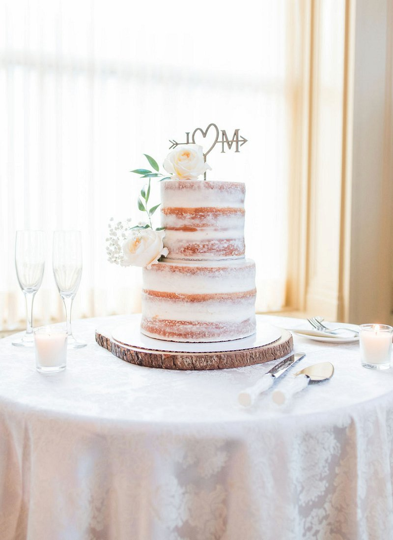 Semi naked tiered wedding cake on rustic wood slab with custom monogram cake topper