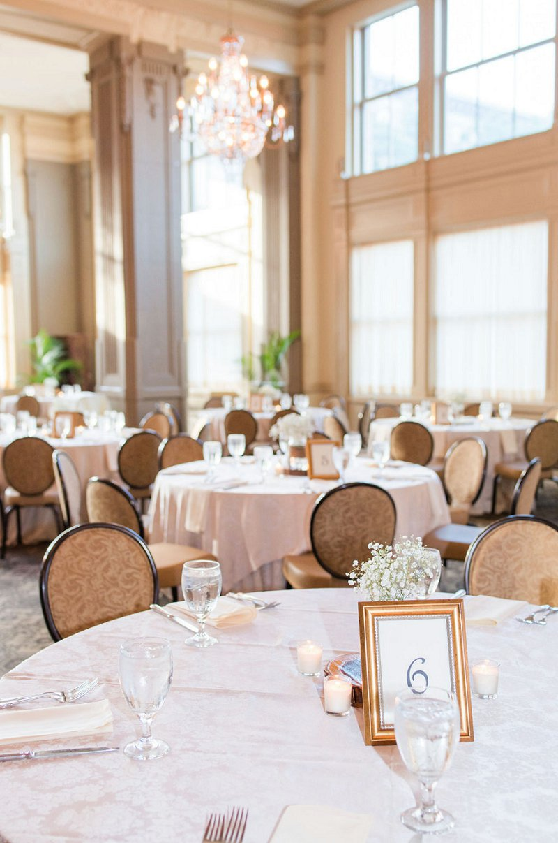 Classic ballroom wedding reception with babys breath centerpieces and gold frame table numbers