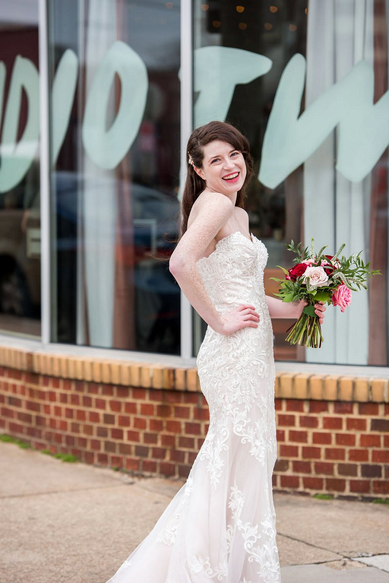 Gorgeous modern bride with freckles wearing a long fitted lace wedding dress and sweetheart neckline