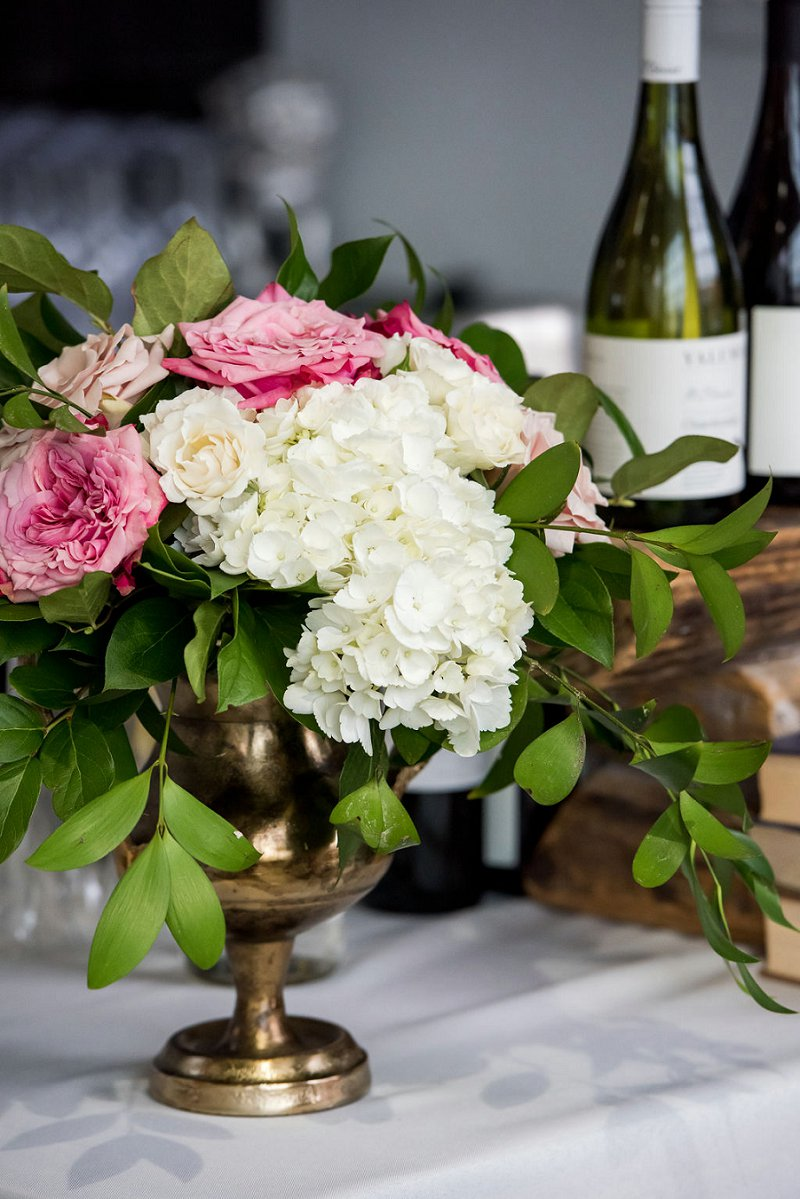 Low wedding centerpiece with white hydrangea and pink garden roses for a chic modern industrial wedding