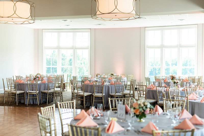 Peach and gray wedding reception tables with low floral centerpieces