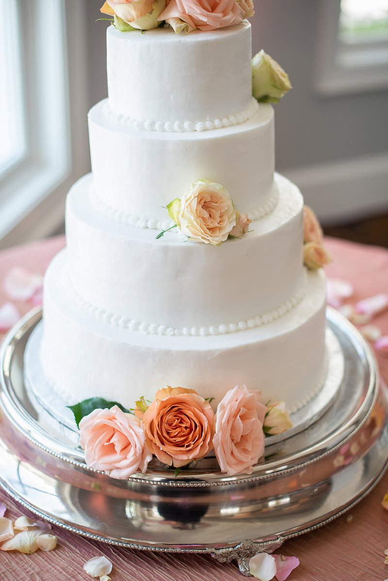 Classic white tiered wedding cake with peach roses and flowers