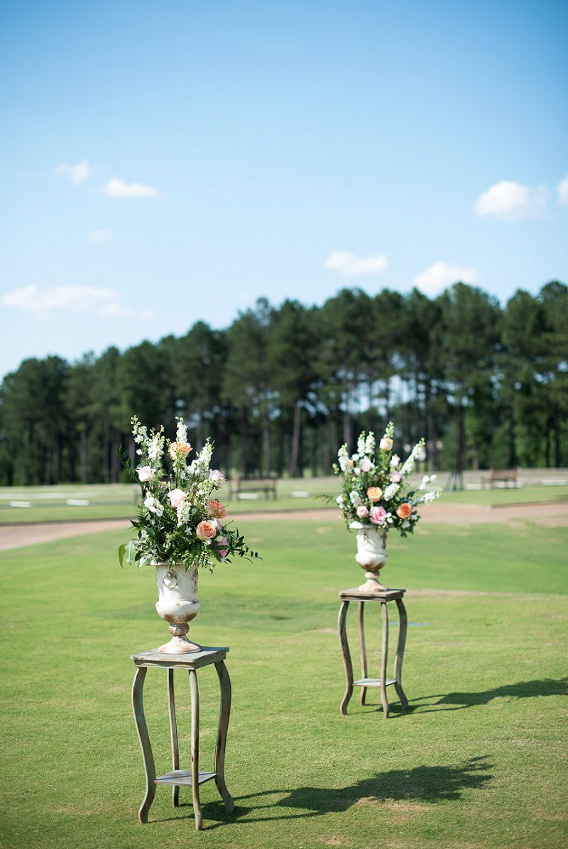 Classic floral altar pedestals for wedding ceremony on the golf course