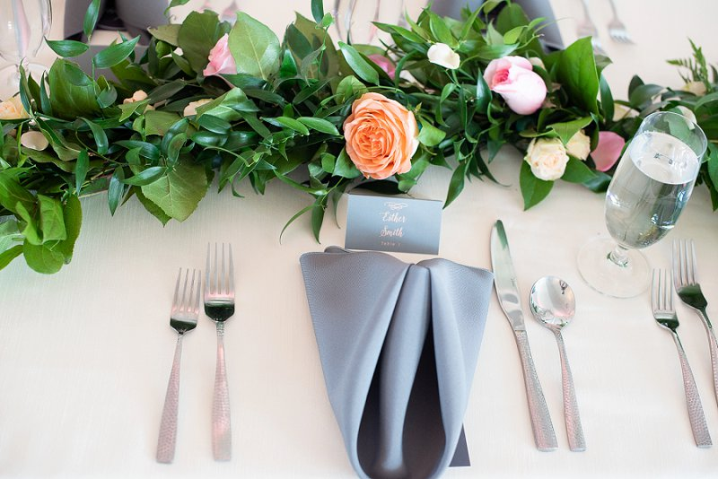 Peach wedding flowers and garland and gray napkins for classic wedding reception decor