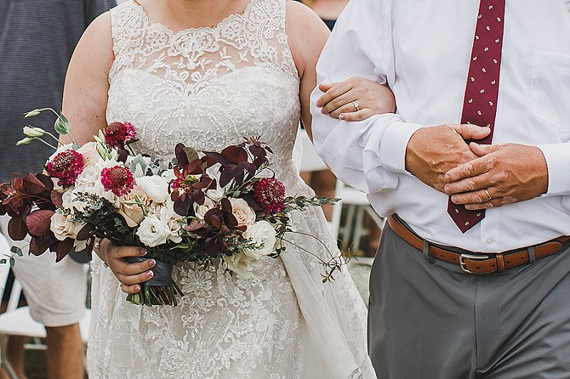 Bride walking down the aisle with her dad and lovely wedding bouquet at fall wedding