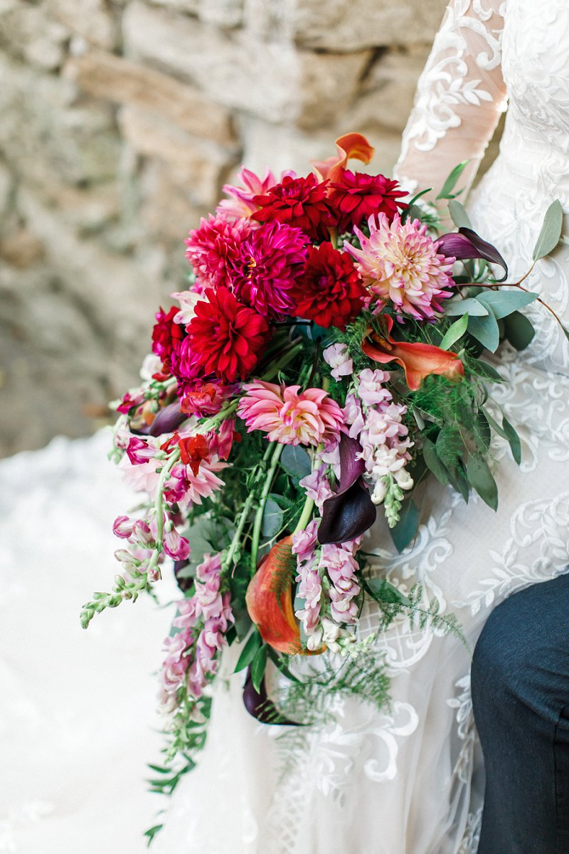 Beautiful fall inspired cascading bridal bouquet with dark pink dahlias and purple calla lilies for the ultimate dramatic jewel toned floral statement