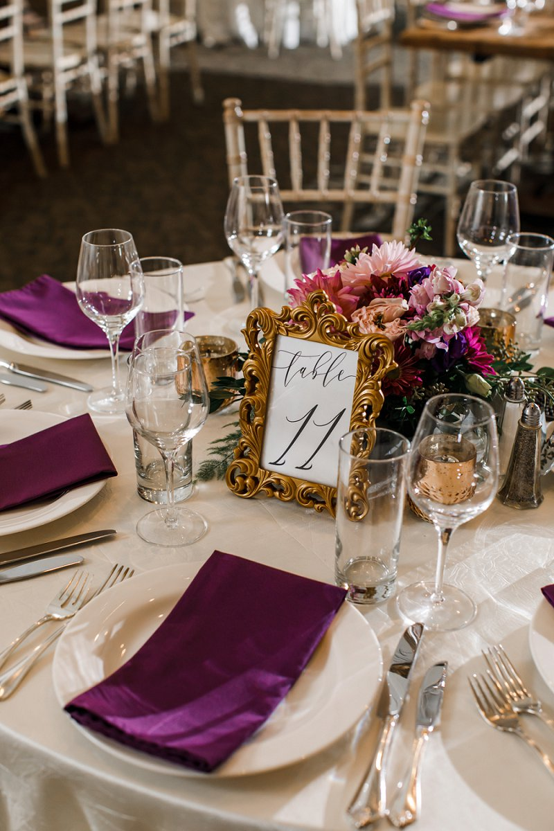 Vintage inspired wedding table number in elegant gold frame decorated with small jewel toned wedding centerpiece