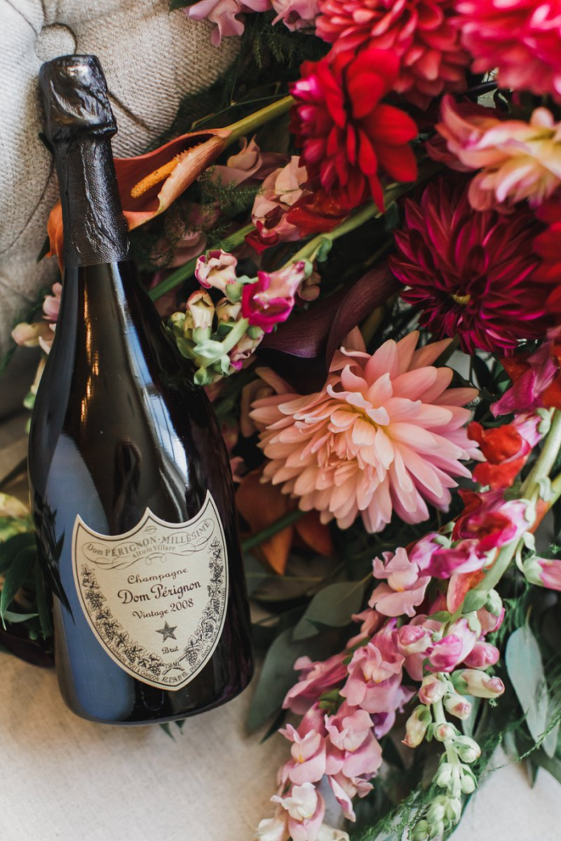 Gorgeous fall cascading wedding bouquet with orange calla lilies and Dom Pérignon anniversary champagne gift for vintage wedding details