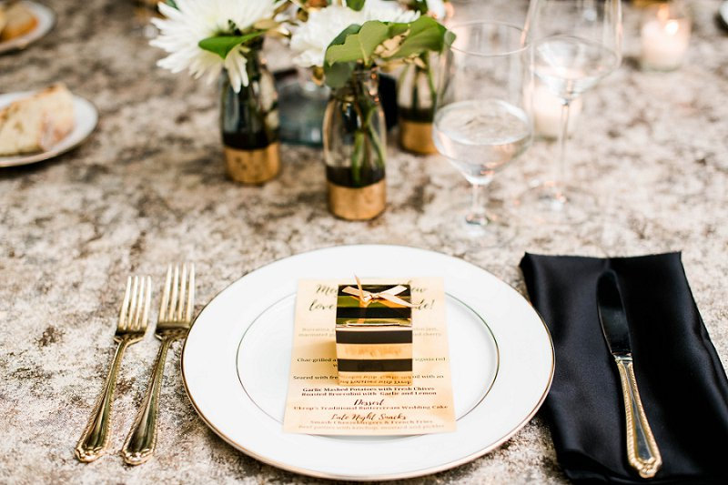 Classic black and white New Years Eve wedding guest table setting with black napkins and gold tablecloths