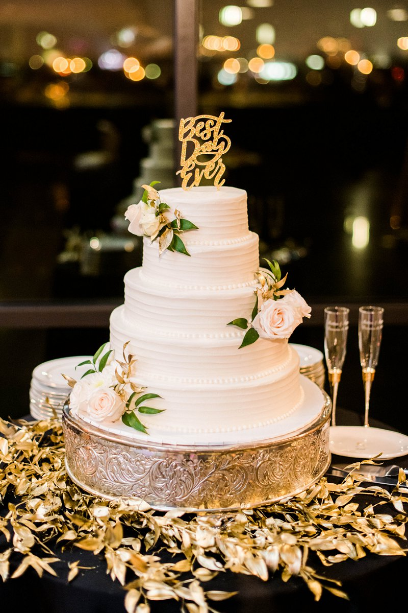White tiered wedding cake with gold Best Day Ever cake topper and white rose decorations surrounded by gold painted greenery