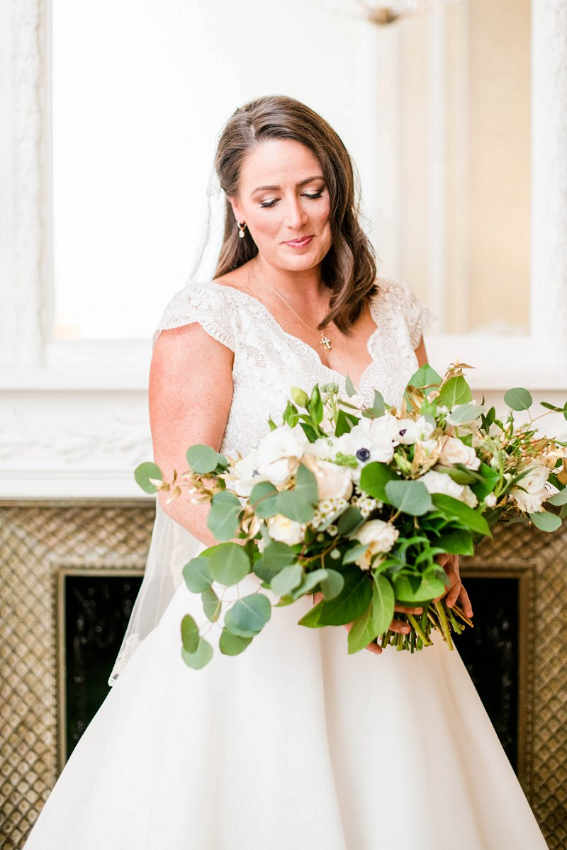 Beautiful mature bride with natural makeup and large wedding bouquet with anemones and greenery