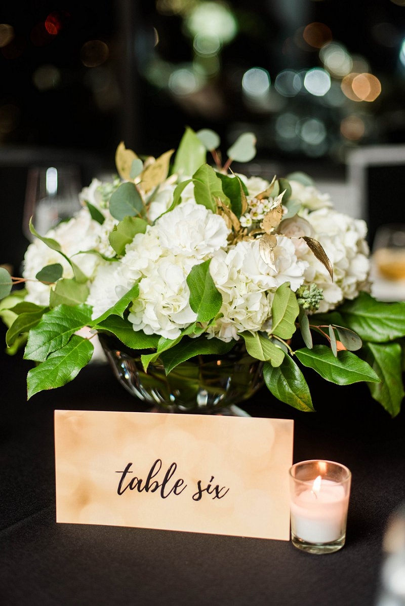 Low wedding centerpiece with white hydrangea flowers and greenery for New Years Eve wedding