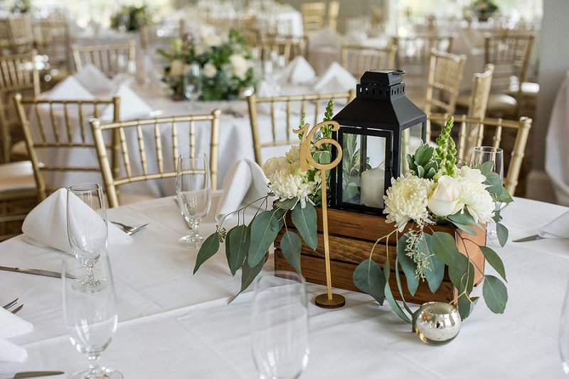 Simple handmade wedding reception centerpiece with wooden box and black lantern surrounded by flowers with gold table number
