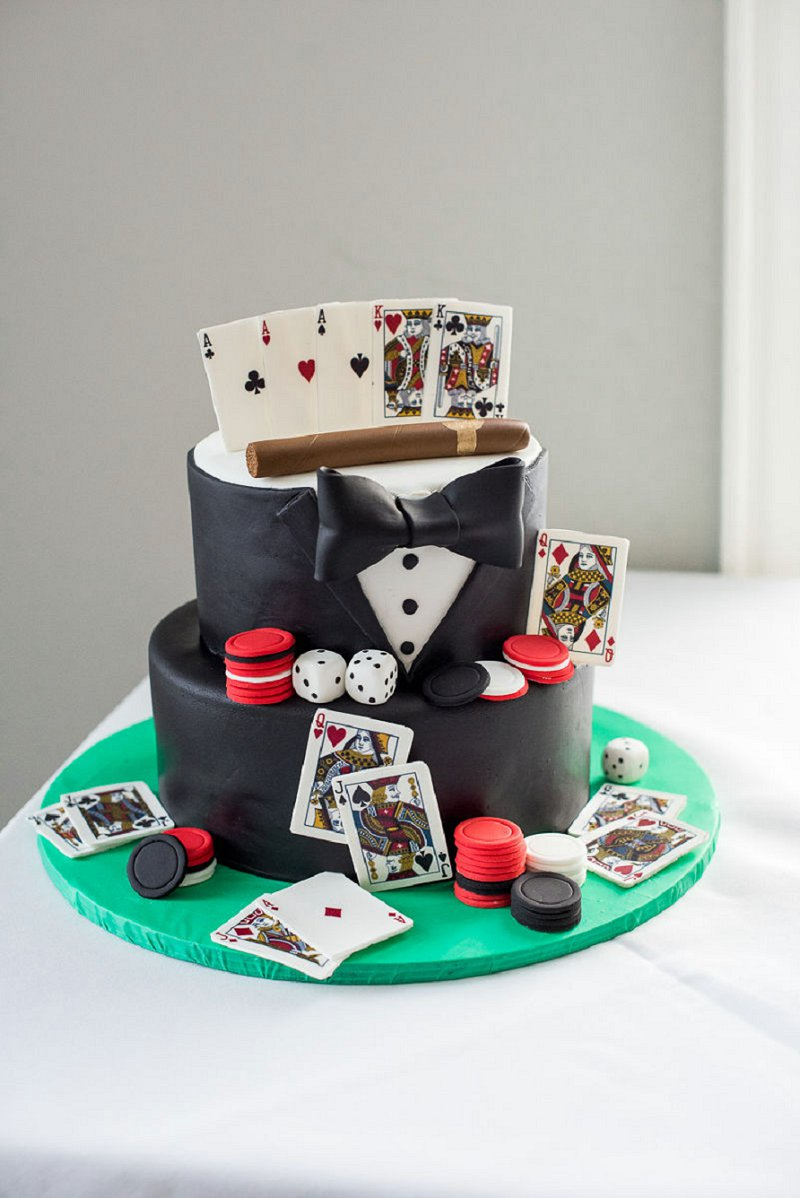 Fun casino themed groom wedding cake with playing cards poker chips and cigar