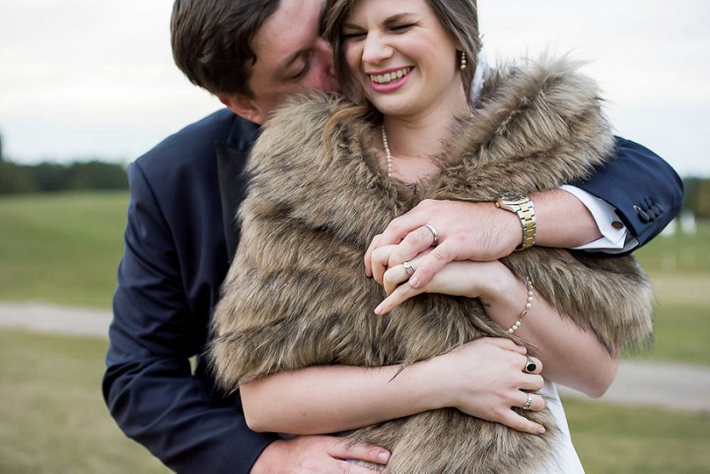 Cold weather wedding with bride wearing a faux fur stole and groom hugging her at Independence Golf Club outside of Richmond Virginia